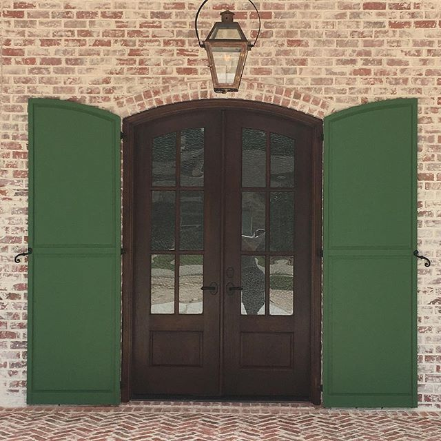 What a unique combo, green shutters with a arched door and brick. Can't forget about the #Bevolo gas lantern!
