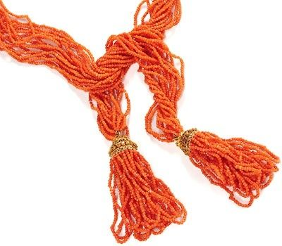 Georgian Coral Tassel Sautoir Necklace circa 18400. In three part form, each section is comprised of five seemingly never-ending looped strands of red-orange coral beads twisted and turned into a loose weave of ten lengths. Tassels are capped with fine 15k yellow gold cannetille work of open lace like finials. The top of each cap is ornamented a grape leaf motif symbolizing a celebration of life and a central band of ornate gold wire rosettes. $3950