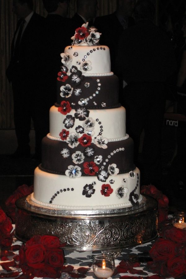 Wedding cake with flowers done with a panisy cutter and thread wrapped around a finger and then secured onto wire. Crystals were placed in the center of each flower.