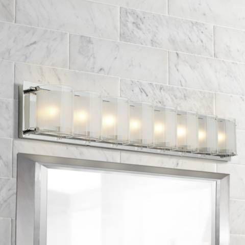 A bold, geometric bath light fixture illuminates a contemporary bath