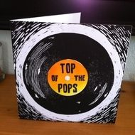 """An original lino print 'Top of the Pops' Father' s Day card featuring an old style 45 record. The card is printed in black ink, with the record label in bright orange and yellow ink. It measures 152mm x 152mm (6"""" x 6"""") and comes with a plain ..."""