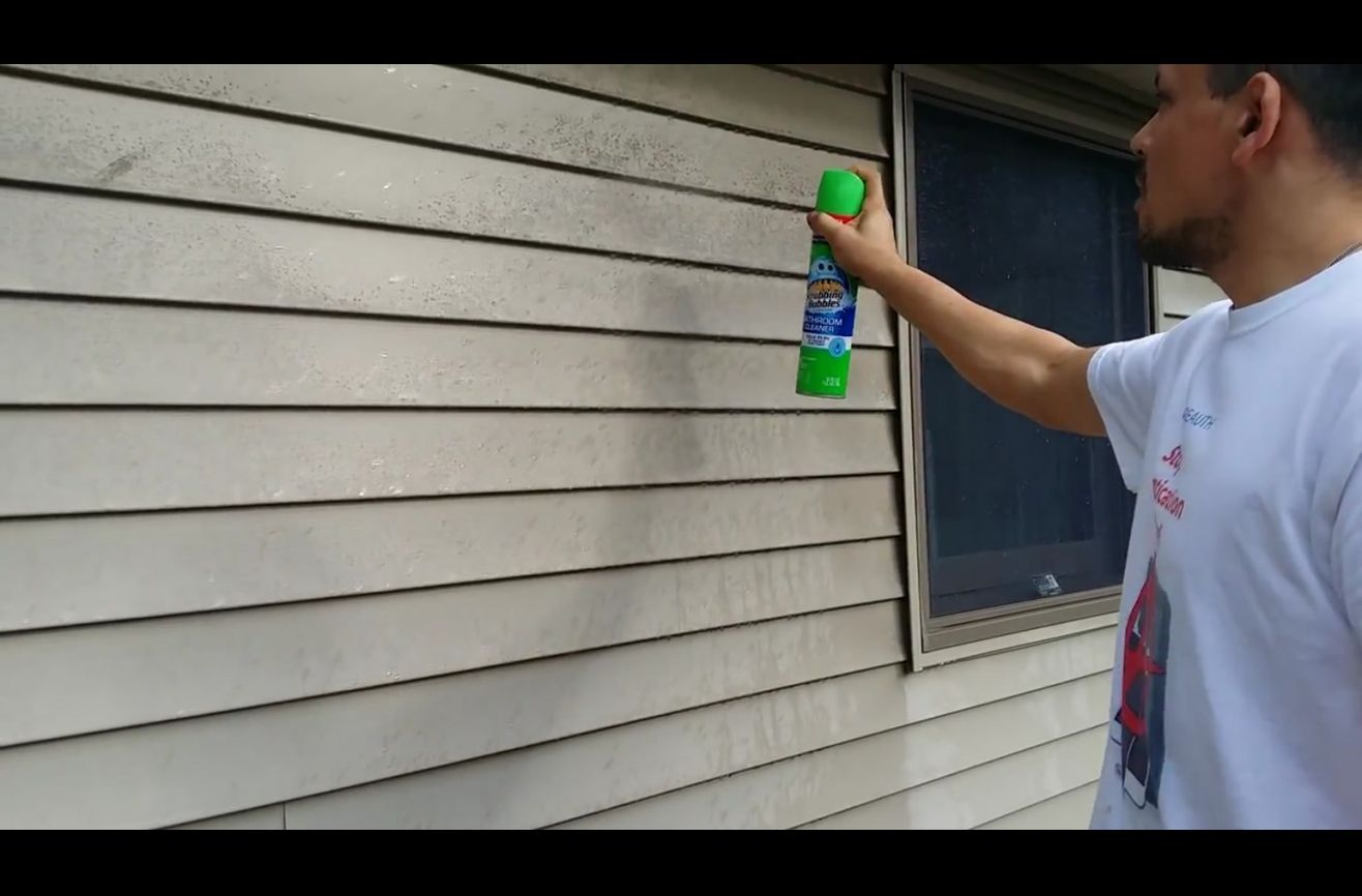 He sprays household cleaner on his vinyl siding this