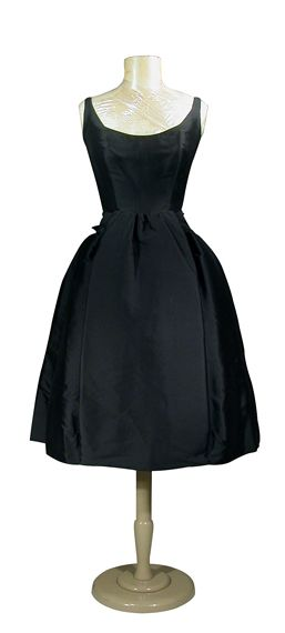 Lanvin Castillo Black Gros de Londres Cocktail Dress   French, 1950s   The full controlled skirt with stitched down center front inverted pleat, attached self sash fastening at back with self bow, decollete neckline, darted bust, interior foundation, black tulle petticoat with chantilly lace trim, size 4, labeled: Jeanne Lanvin/Paris and Castillo.