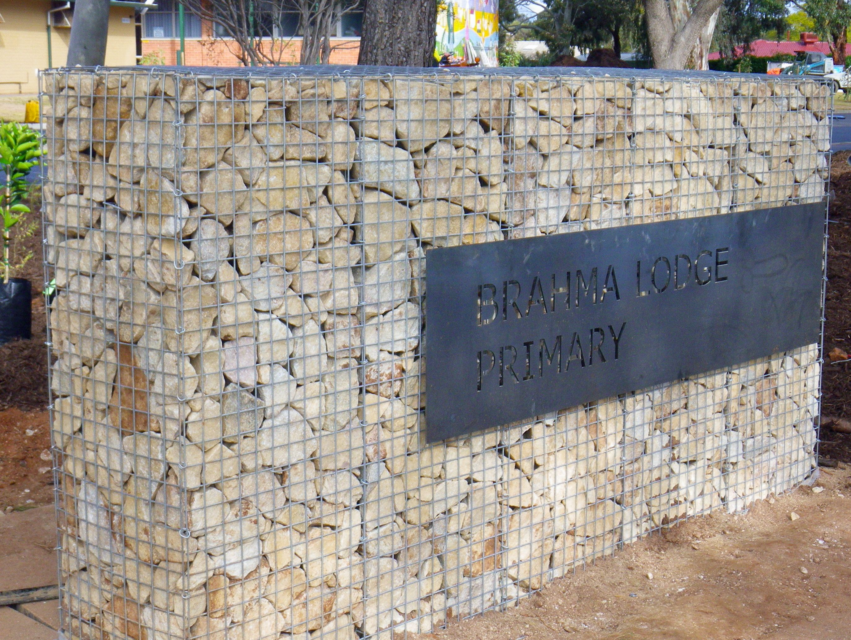 Stainless steel sign plaque applied to a Gabion wall built by