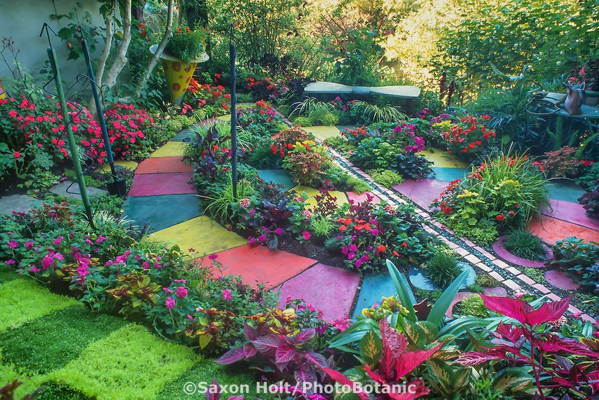 multicolored cast concrete pavers in whimsical spiral path in backyard garden room with colorful