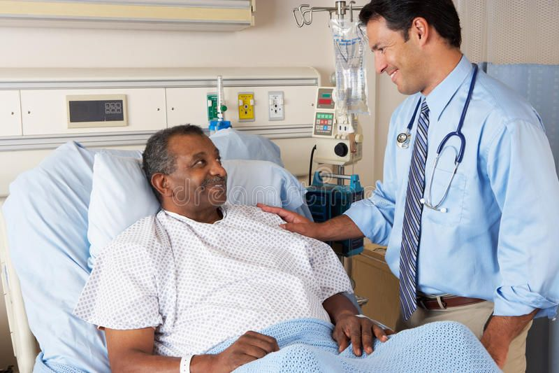 Doctor Visiting Senior Male Patient On Ward Male Doctor Visiting
