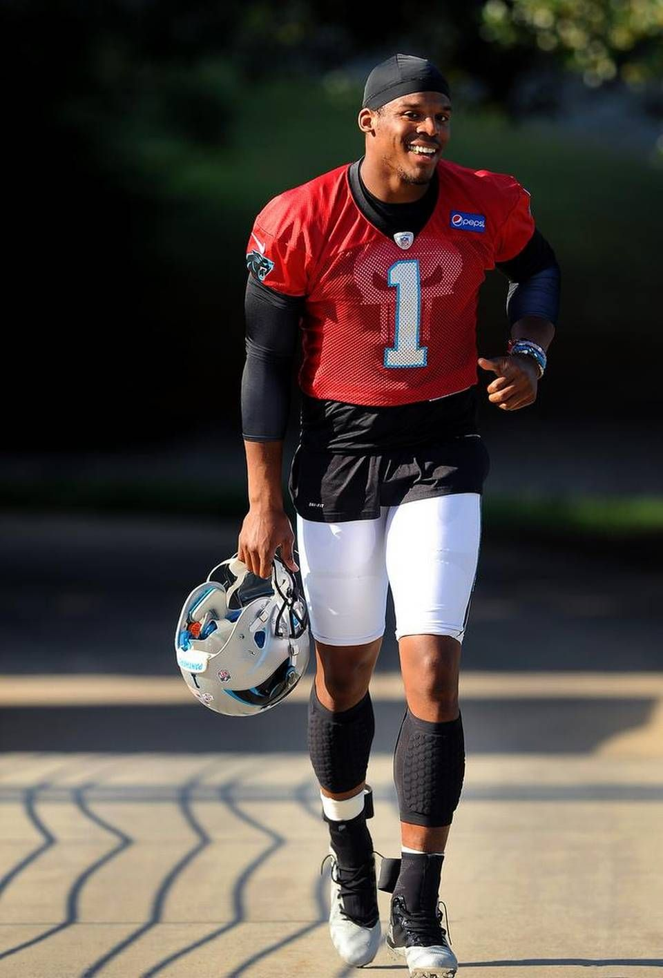 Carolina Panthers quarterback Cam Newton smiles as he jogs to practice on Tuesday, September 1, 2015.