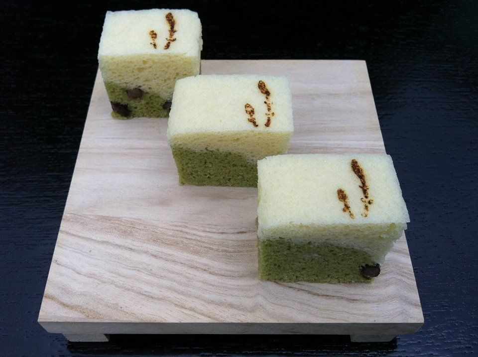 "These steamed cakes are made primarily from white bean paste with a small amount of wheat and rice flour. Matcha flavors the green layer with a few candied adzuki beans representing the ""seeds"" of spring. The flavor is delicate; not too sweet. The branded design is of Horsetail shoots, or Knotweed, which the Japanese forage for in the spring and is a seasonal culinary treat."