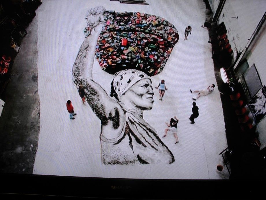 """One of the trash-pickers' portraits that was blown up and """"painted"""" using items from the Rio landfill."""