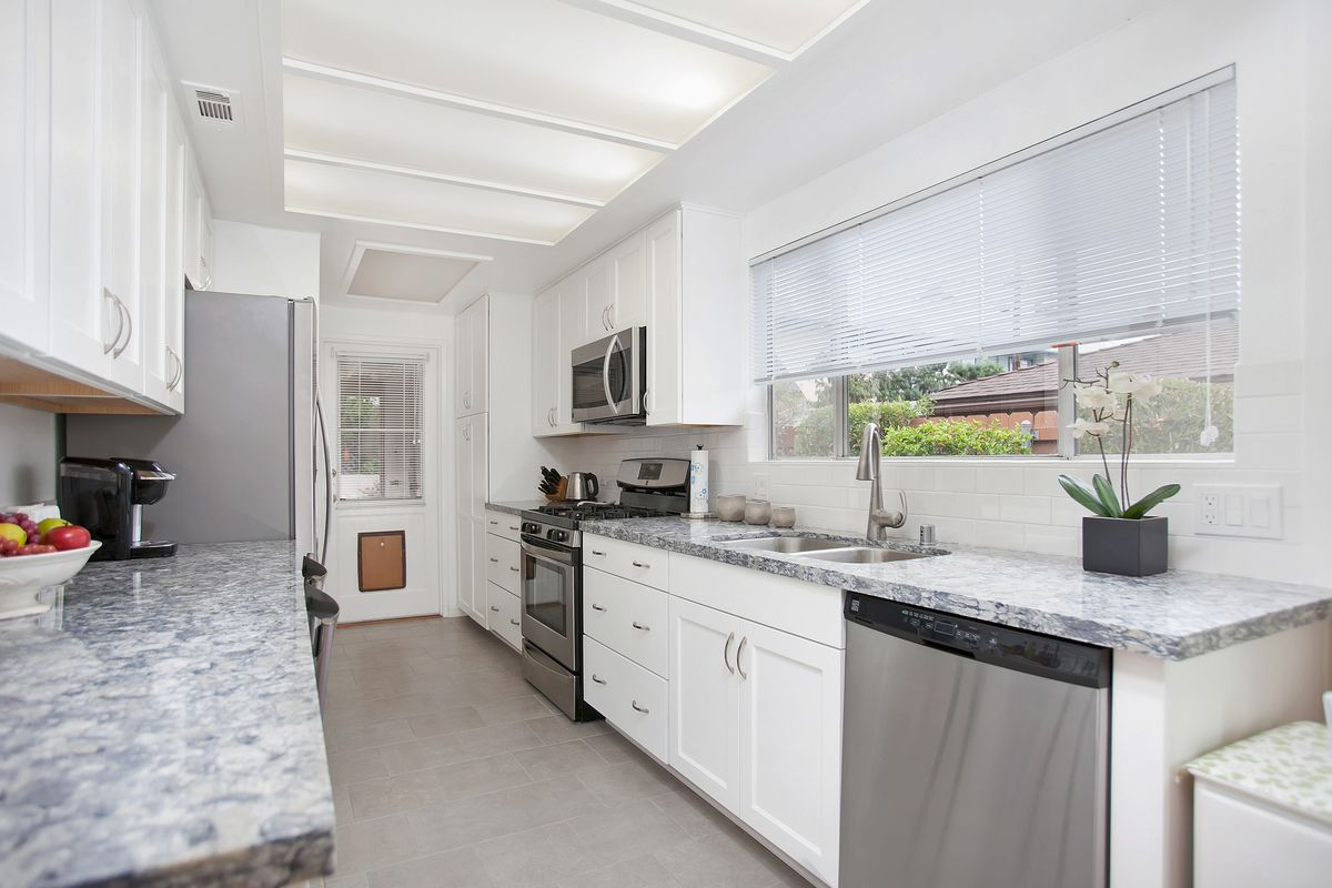 White painted maple shaker style cabinets lighten up this kitchen