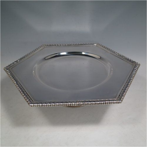 An Antique Sterling Silver very heavy tazza cake dish, having a plain hexagonal body, with a gadroon border, and sitting on a pedestal foot with applied cut-card work and hand-chased fluting. Made by Sebastian Garrard of London in 1911. The dimensions of this fine hand-made antique silver tazza dish are height 8 cms (3 inches), width of plate 31 cms (12.25 inches), and the weight is approx. 1,425g (46 troy ounces).