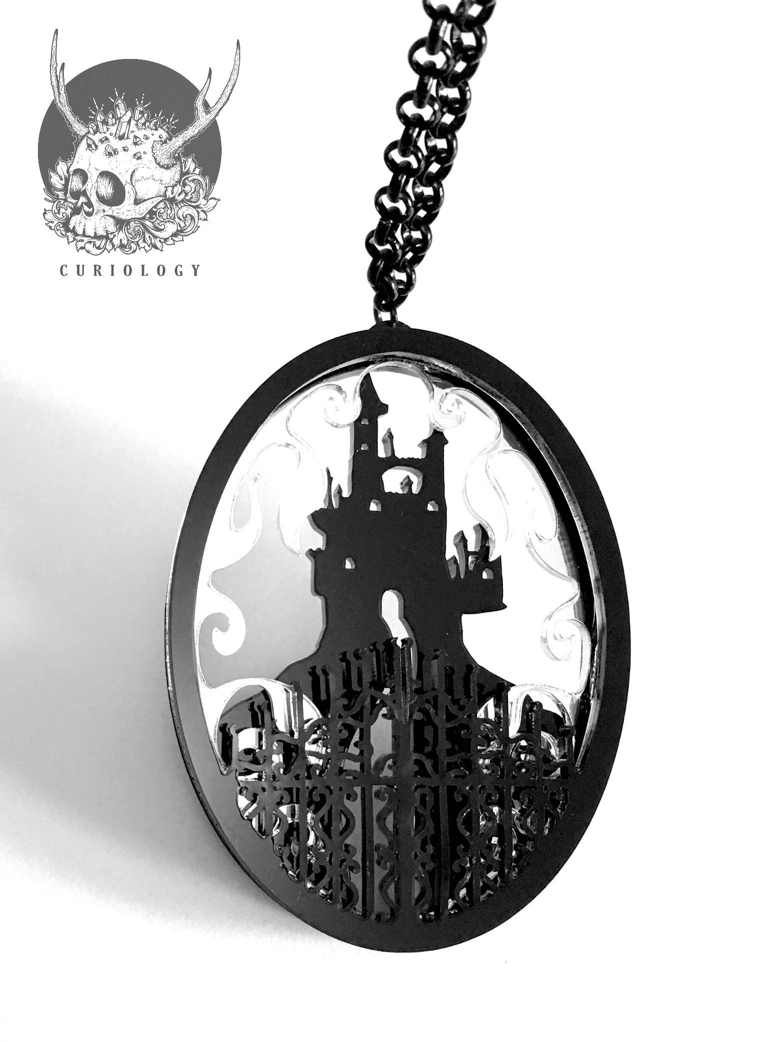Faerie Castle 3 layered pendant. Material - Acrylic.Two layer black, middle layer mirror.Pendant size 7.5cm/3 inches.Standard options are black/silver nickel free 18 inch chains.Chains can now be upgraded to sterling silver. Please visit the Chain Upgrades section to add this to your order.Prices are as follows...16 inches   £5.0018 inches   £6.0020 inches   £6.50Black organza necklaces or faux leather cords can be added for no extra charge on request. Please leave us a note if you require…