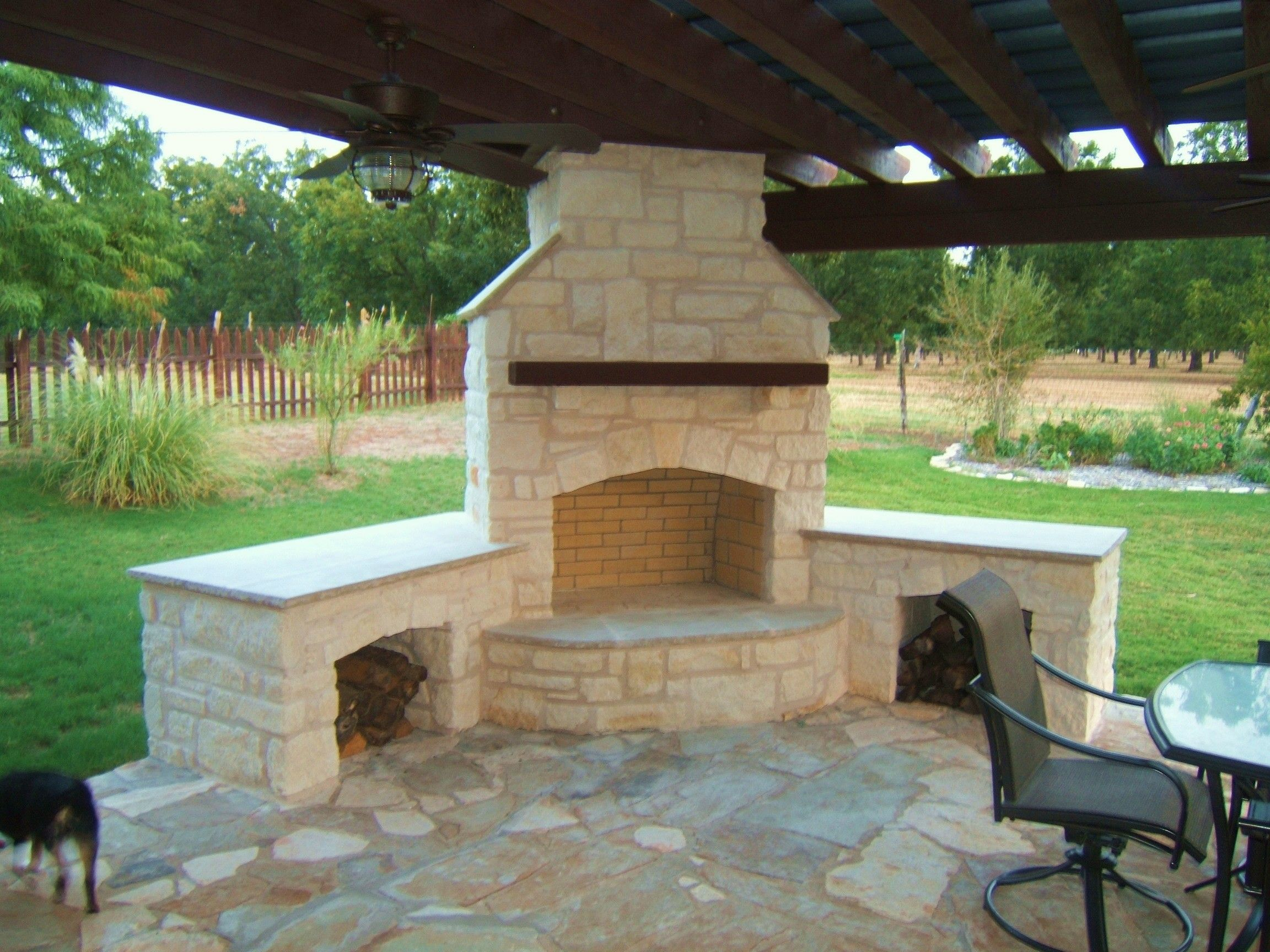 outside kitchen with grill and stone corner fireplace under the