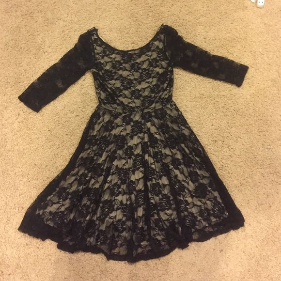 Black Floral Lace Fit and Flare Skater Dress This dress is a black floral lace, and would be very pretty on any skin tone. For the body and skirt of the piece the lace is layer over a medium beige fabric, and the sleeves are black lace. The fit is nice through the top, and the skirt length is a decent length for many heights. Deb Dresses Midi