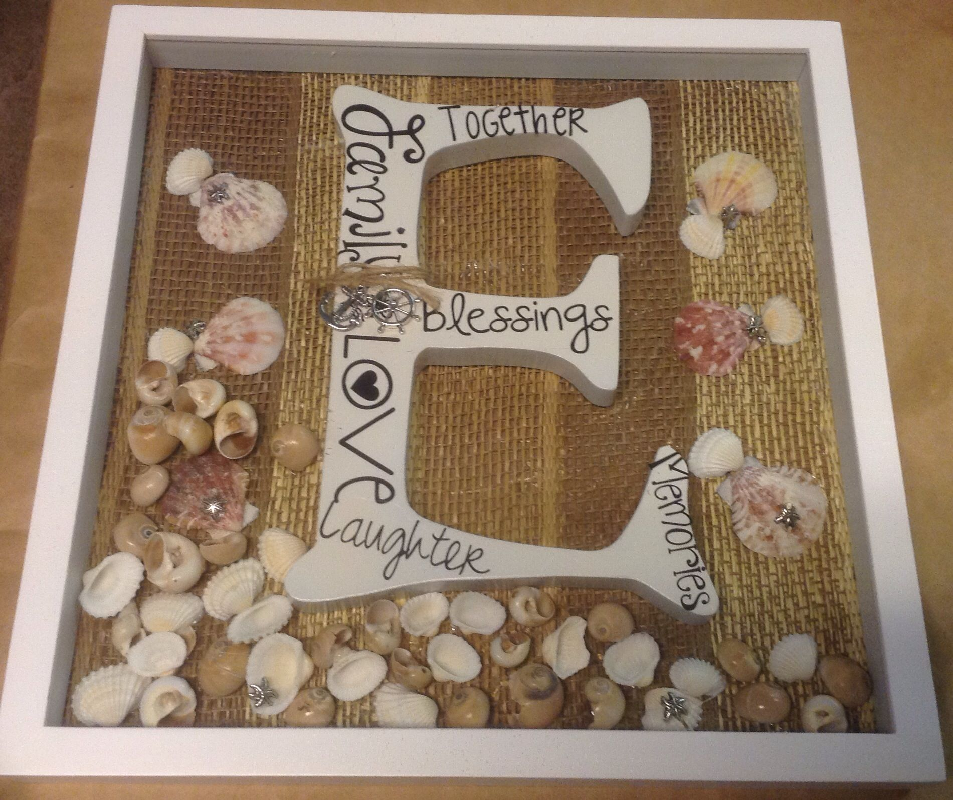 Shadow box frame with large wood initial, decorated with sea shells. Burlap background.