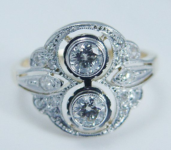 This gorgeous antique circa 1910s ring is finely crafted in solid 18K Yellow and white gold for the top (carefully tested and guaranteed). There are two Old miner cut diamonds in the center (.23 carat each), and fourteen miner cut diamonds set on the sides. The diamonds are estimated to be very clean VS-1 clarity and GH color for the total weight .60 carat.