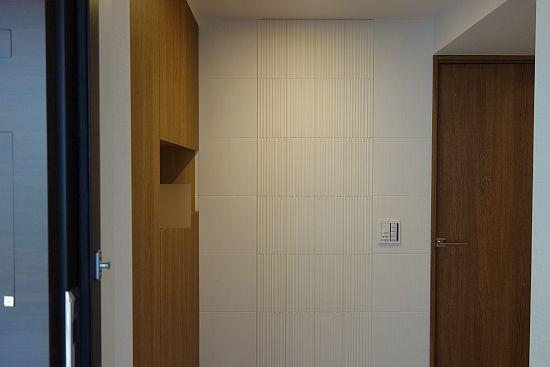 玄関ドア開けて正面の壁にエコカラットプラス グラナスヴァーグと