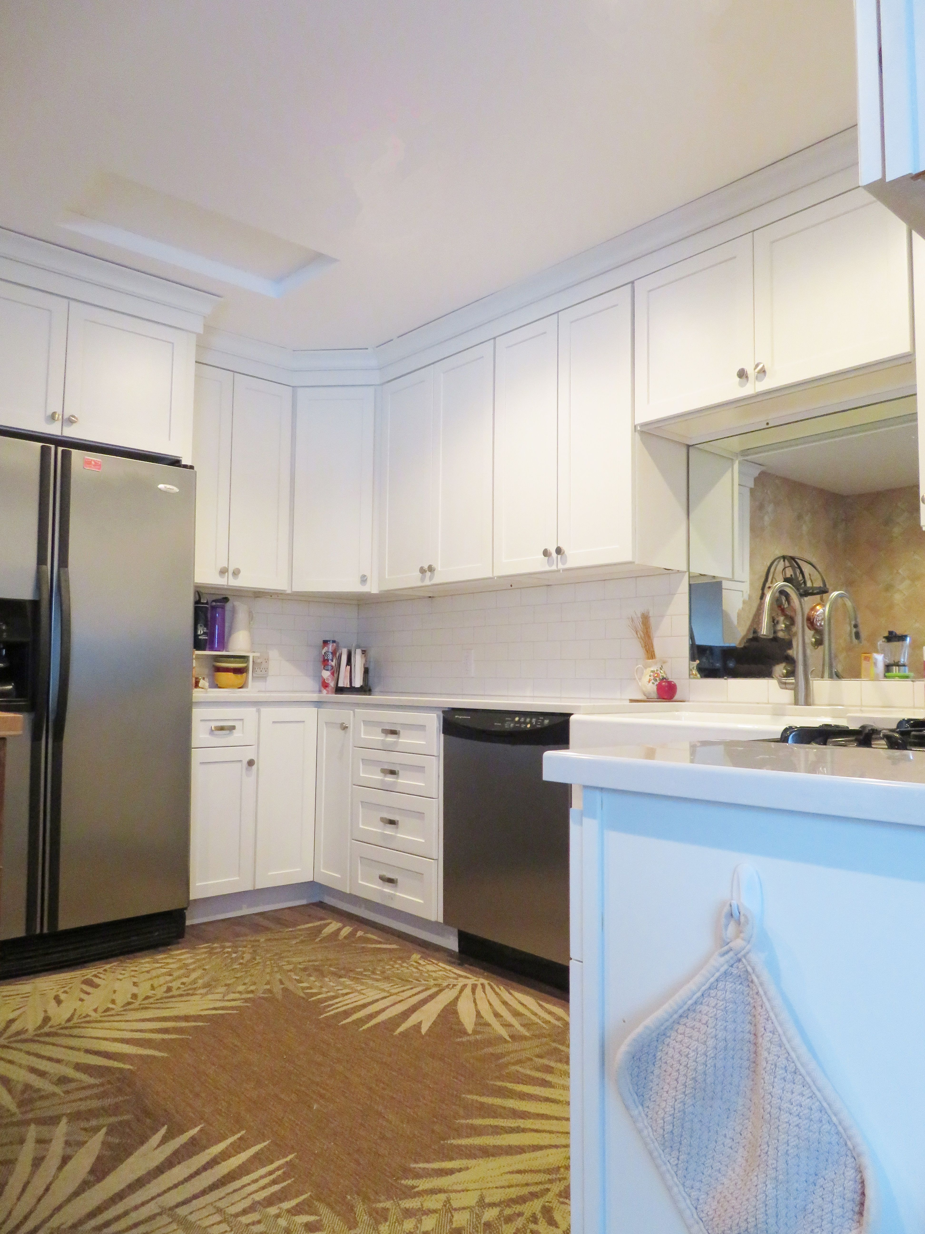 Small White Kitchen made bigger by a mirror. Cabinetry: Homecrest ...