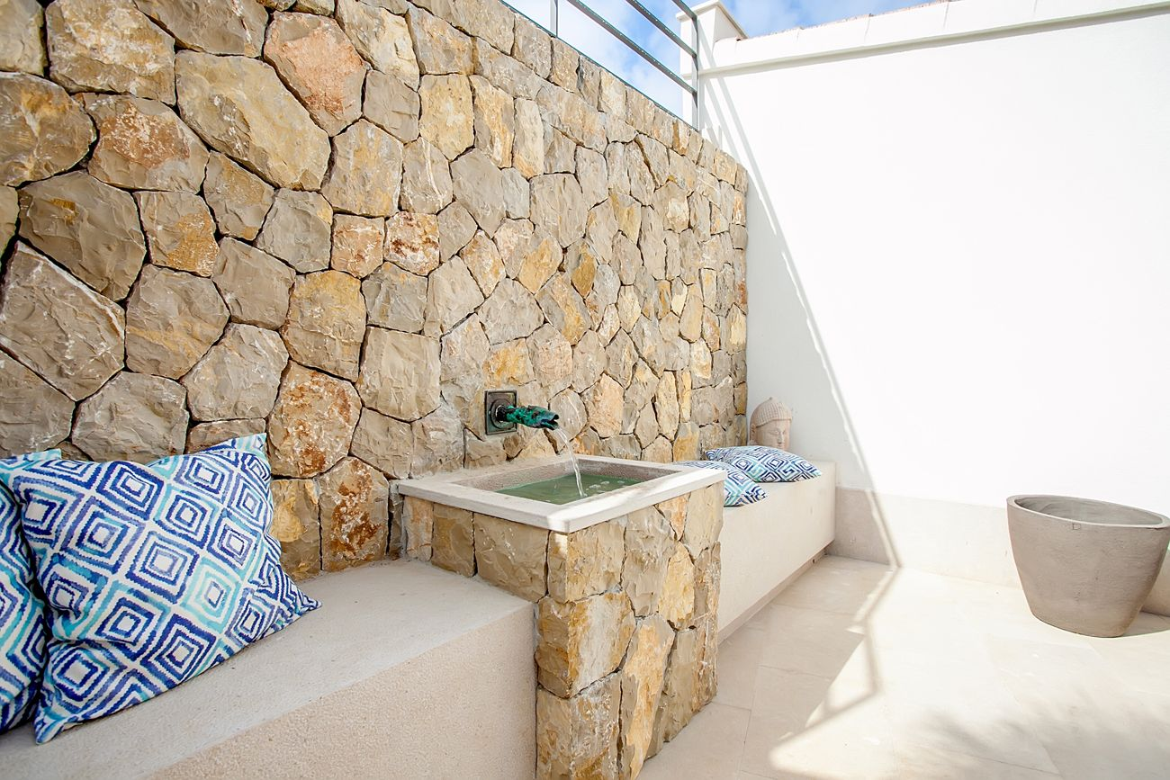 mediterranean stone wall with water play and nice cushions. Black Bedroom Furniture Sets. Home Design Ideas