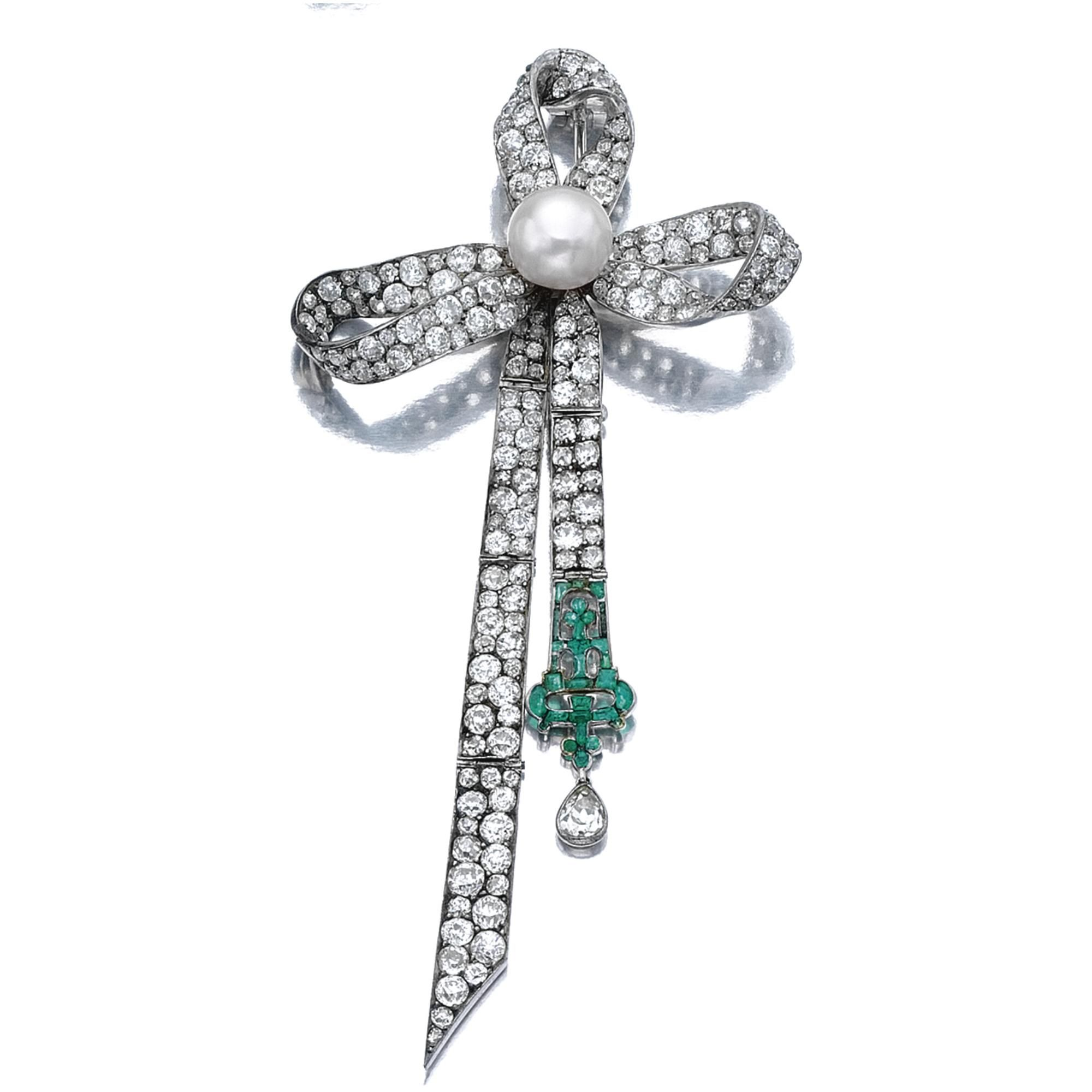 PEARL, EMERALD AND DIAMOND BROOCH Of stylised bow design, set with circular-, single-cut, cushion- and pear-shaped diamonds, to the button-shaped pearl accent, suspending a calibré- and circular-cut emerald detail.