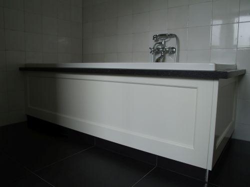 Landelijke badkamer. bad ombouw met houten panelen en rand