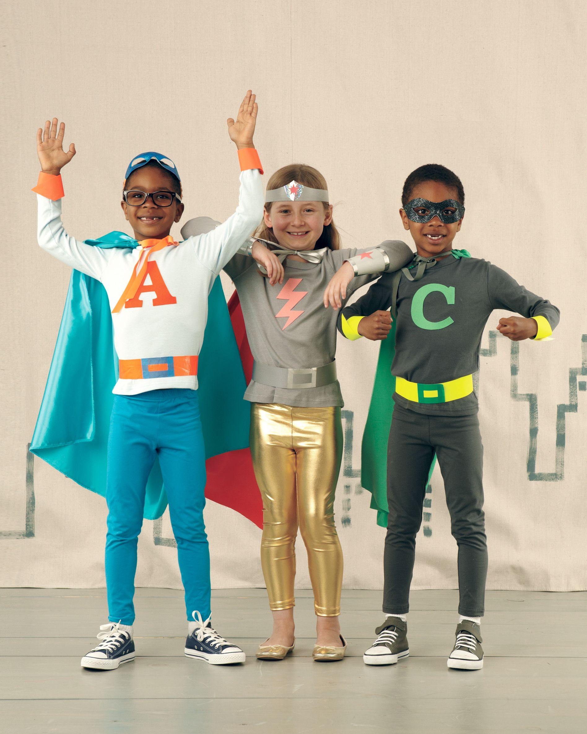 I made my boys a 'wonder twins' costume inspired by these pics.  Their initial on the front, and a lightning bolt and star on the cape.  Lurv it!