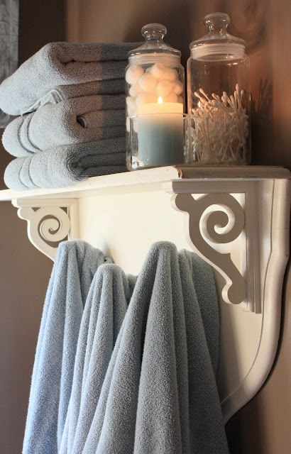 Shelf with hooks for bathroom. Folded towels on top and hang used ...