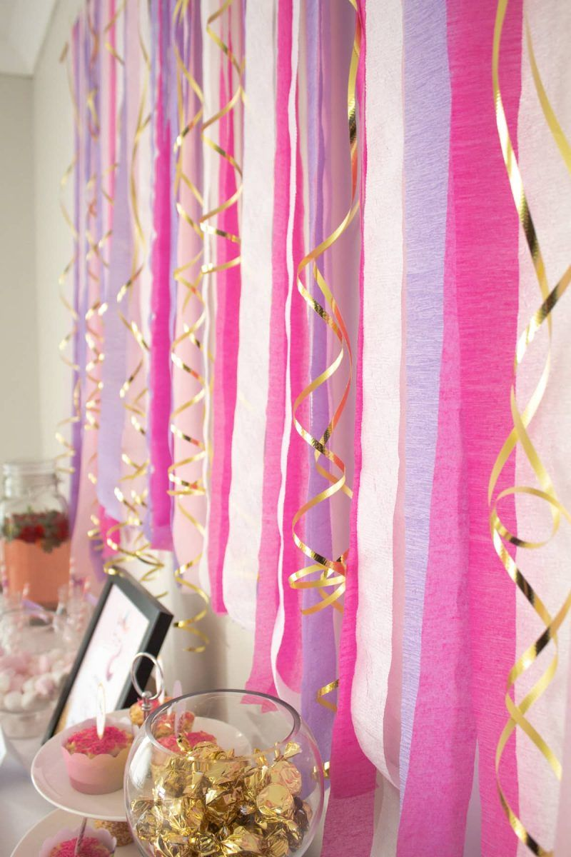 Crepe paper streamer party backdrop | Magical unicorn party plus {FREE} unicorn printables download kit | Printable unicorn themed kit comes with invitation, party sign, cupcake wrappers, cupcake toppers, food signs and straw flags | A Visual Merriment | #freeprintable #party #birthday #unicorn #girlsparty #partydiy #diy #backdrop #streamerbackdrop