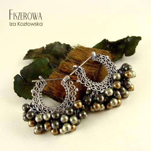 FISZEROWA - Mossy pearls == Urocze, bardzo retro kolczyki wykonane z ażurowych srebrnych baz, w które wpleciono szklane perły Swarovskiego w różnych odcieniach zieleni. Dla podkreślenia secesyjnego charakteru kolczyków, zostały one zoksydowane i wypolerowane.  Długość kolczyków: 2,8 cm. Szerokość kolczyków: 3,2 cm.