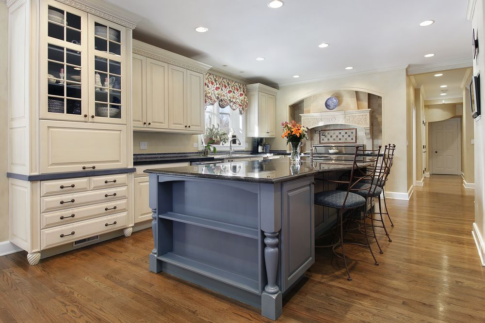 White Kitchen With Custom Cabinetry, Wood Floor And Large Grey Island With  Eat In