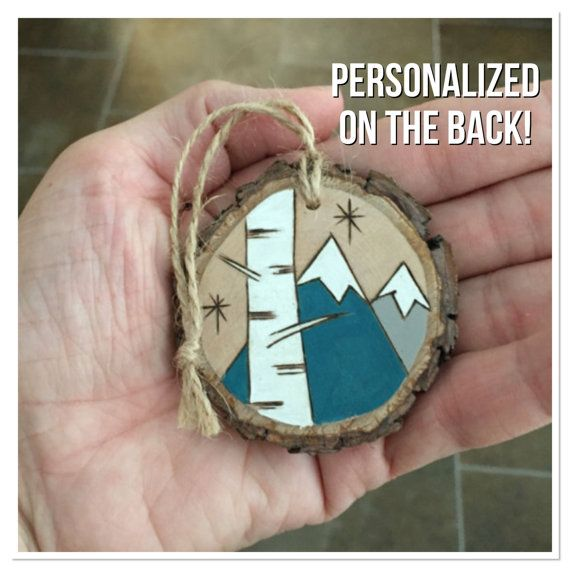 This rustic wood Christmas ornament features an original wood burning on one…