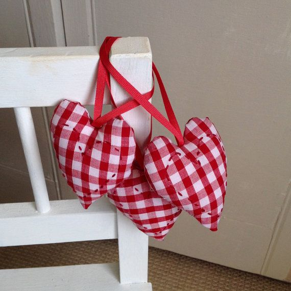 A set of 3 padded hanging heart decorations in a red check gingham fabric with hand stitched decoration.  Lovely hanging on the Christmas tree or as accents to a country kitchen all year round.