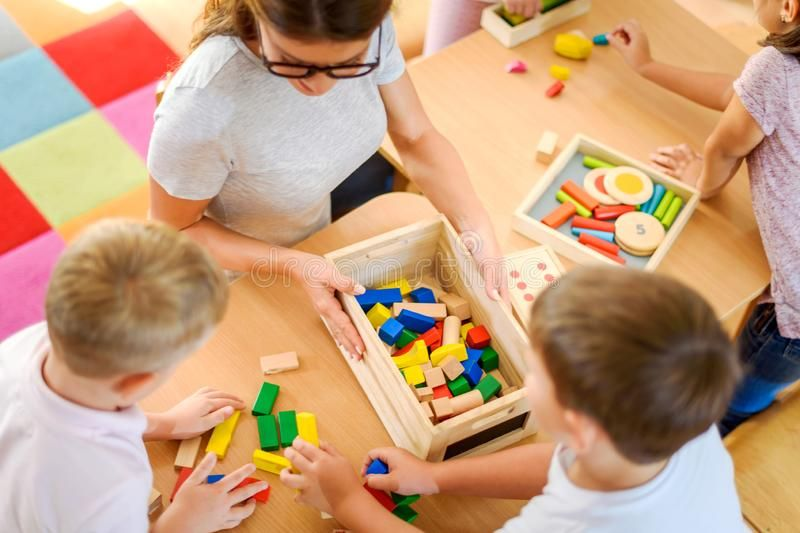 Preschool Teacher With Children Playing With Colorful Didactic