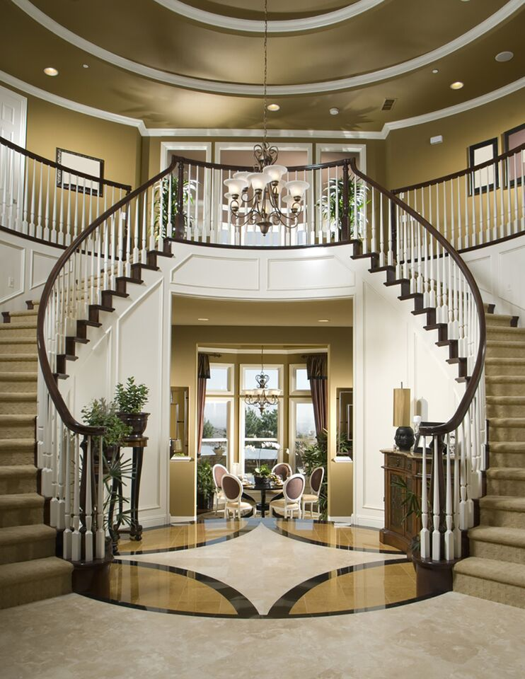 Dual curved staircases really up the luxury of this carpet and tile foyer that leads into a dining room. A chandelier at the center of the two staircases adds the perfect touch.