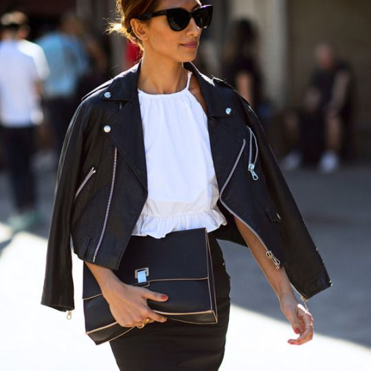 b7c5cb712963 A street style star with a leather jacket draped over her shoulders and a  Proenza Schouler clutch in hand.