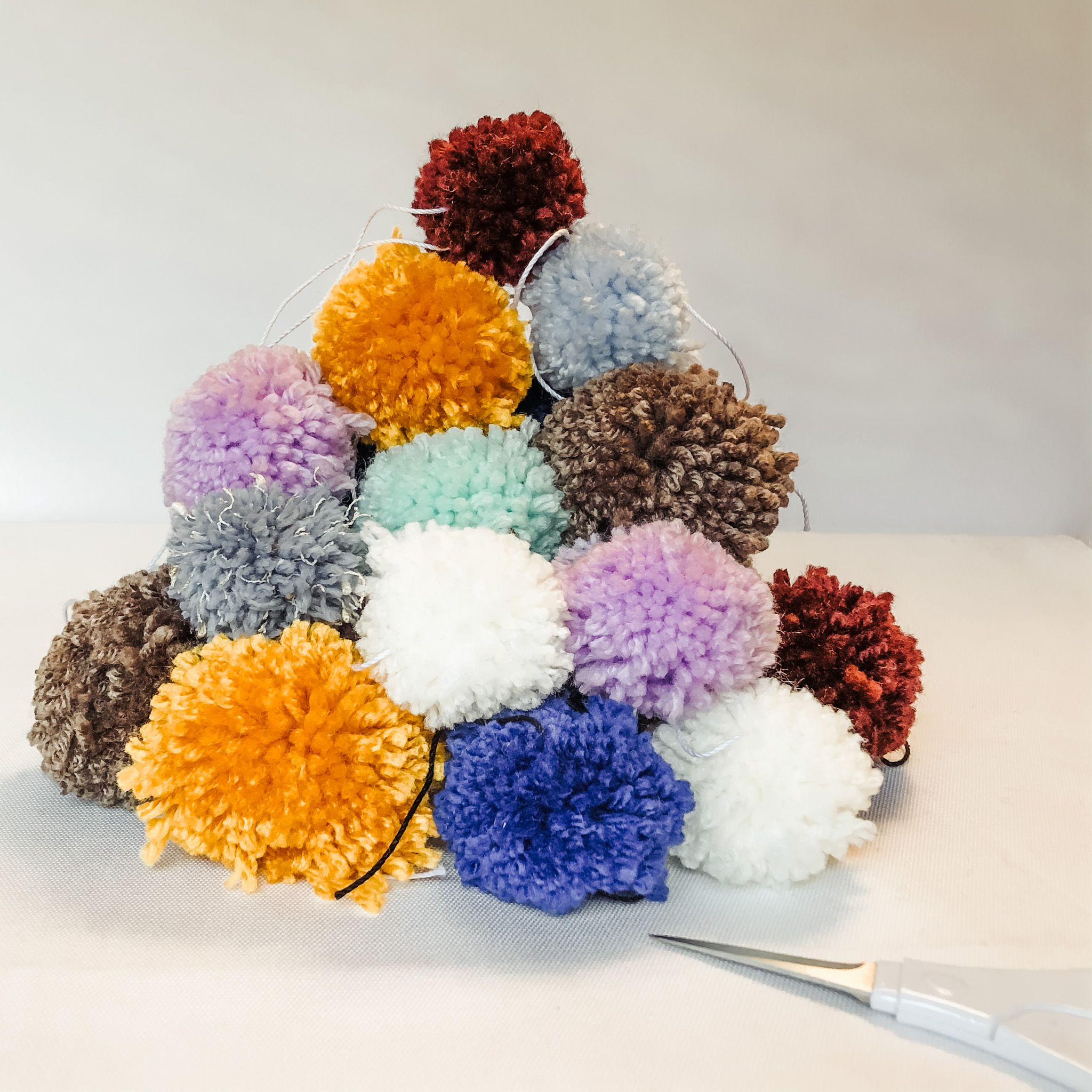 A pile of untrimmed pom poms waiting to be trimmed and turned into earrings. #pompoms #pompommaking #makersgonnamake #pomopmearrings #etsyseller #colorfulyarn #yarncrafts