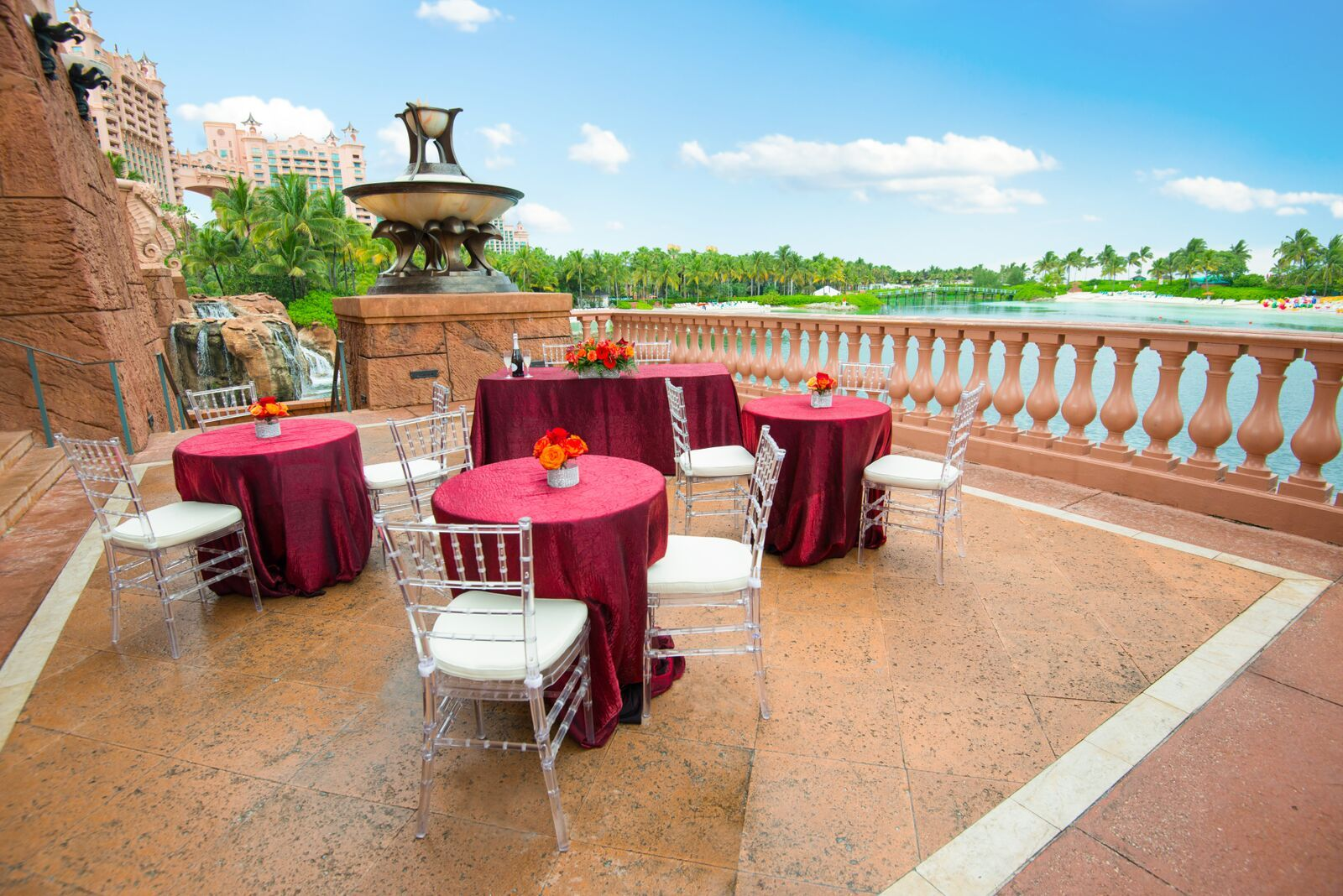 Reception overlooking the beach and pool on Dragon's Patio with bright burgundy linens and clear chivari chairs. #events Atlantis | Bahamas