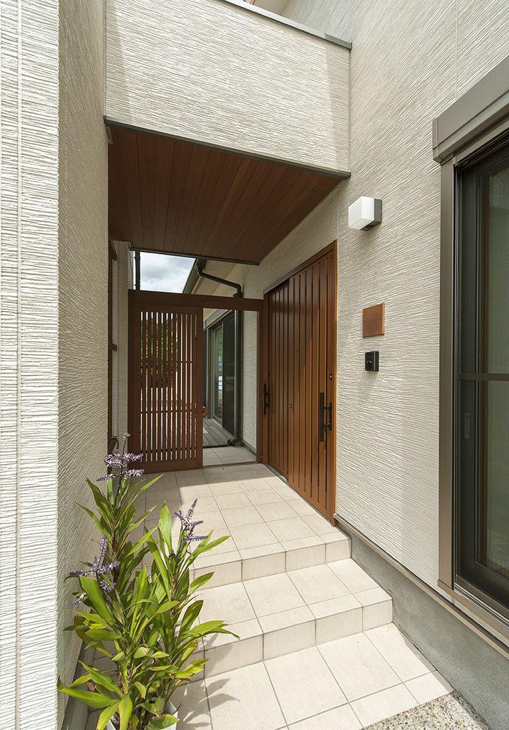 アプローチから右が玄関へ 正面の格子扉を開けばそのままウッドデッキへの導線を設けました 2世帯住宅 間取り リノベーション 平屋 玄関アプローチ