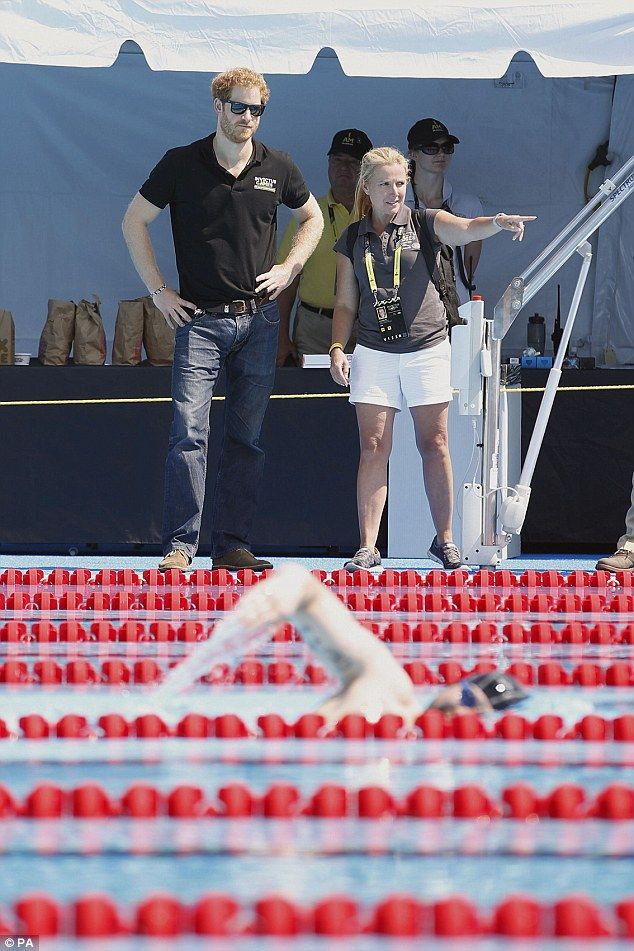 The red-headed prince with the dark shades watches swimmers practice ahead of the Invictus...