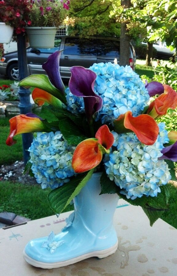 Fun arrangement of colorful lilies and hydrangeas in a powder blue rainboot. Toronto/GTA florist
