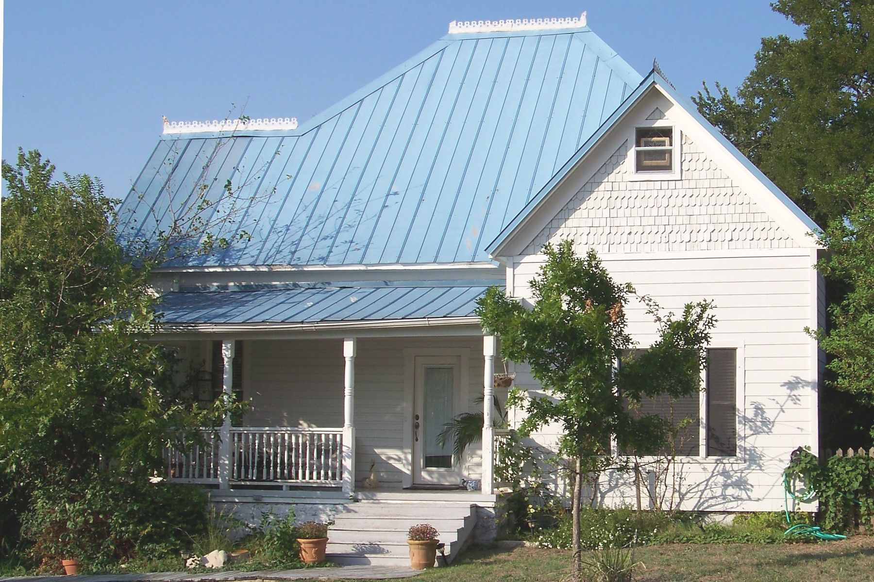This frame house with a blue metal roof was built for h l for Images of houses with metal roofs