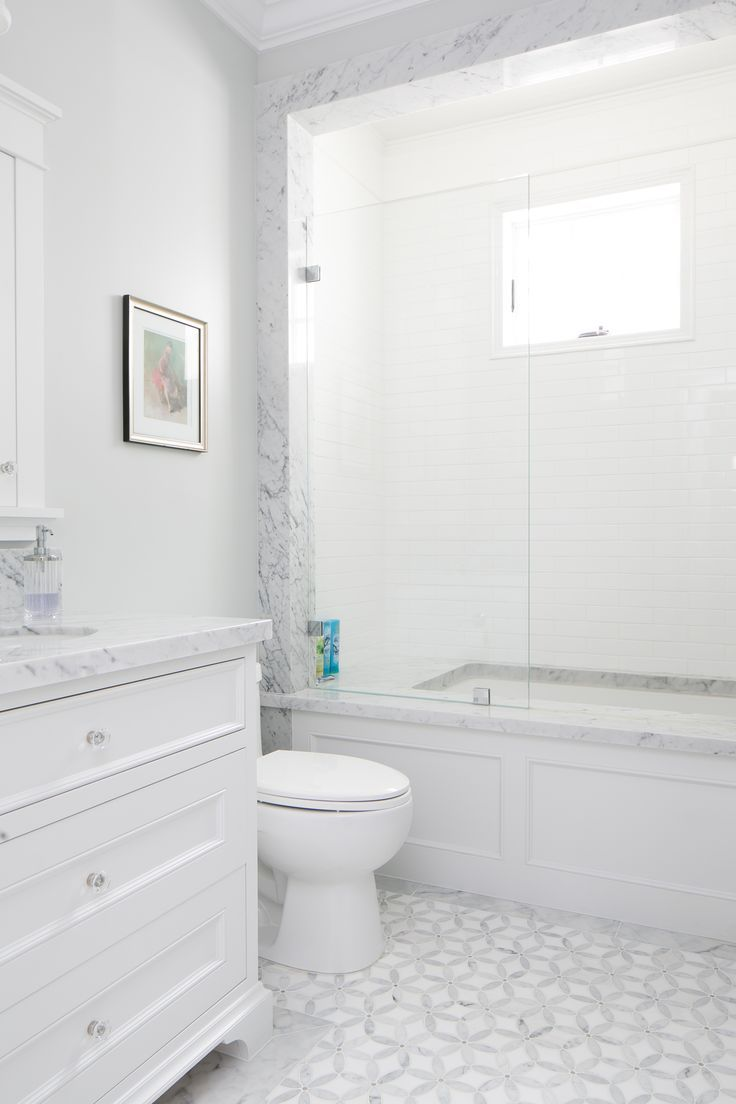 This white bathroom features a unique white and gray tile pattern, a ...