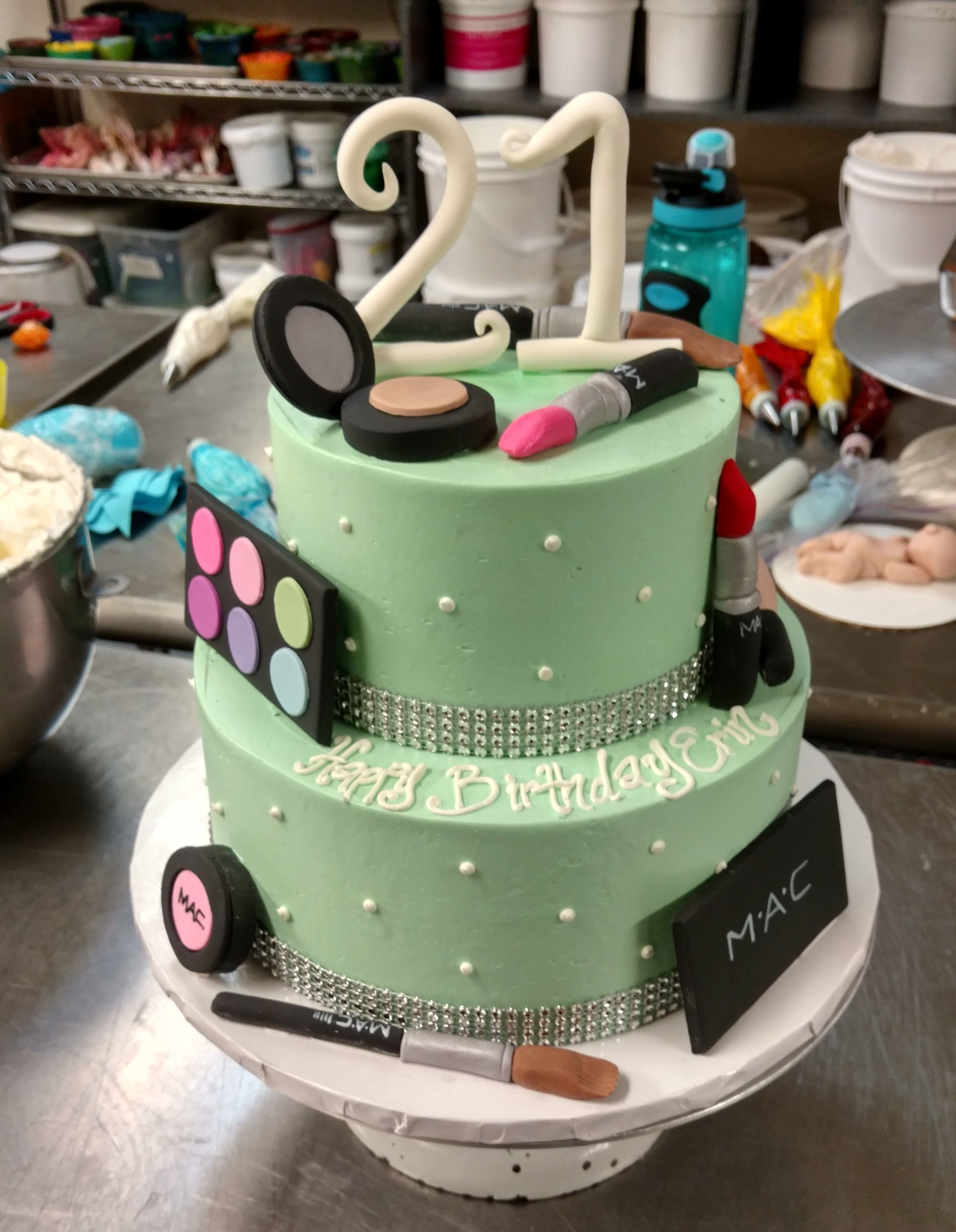 A blingy two tier cake covered in fondant makeup and