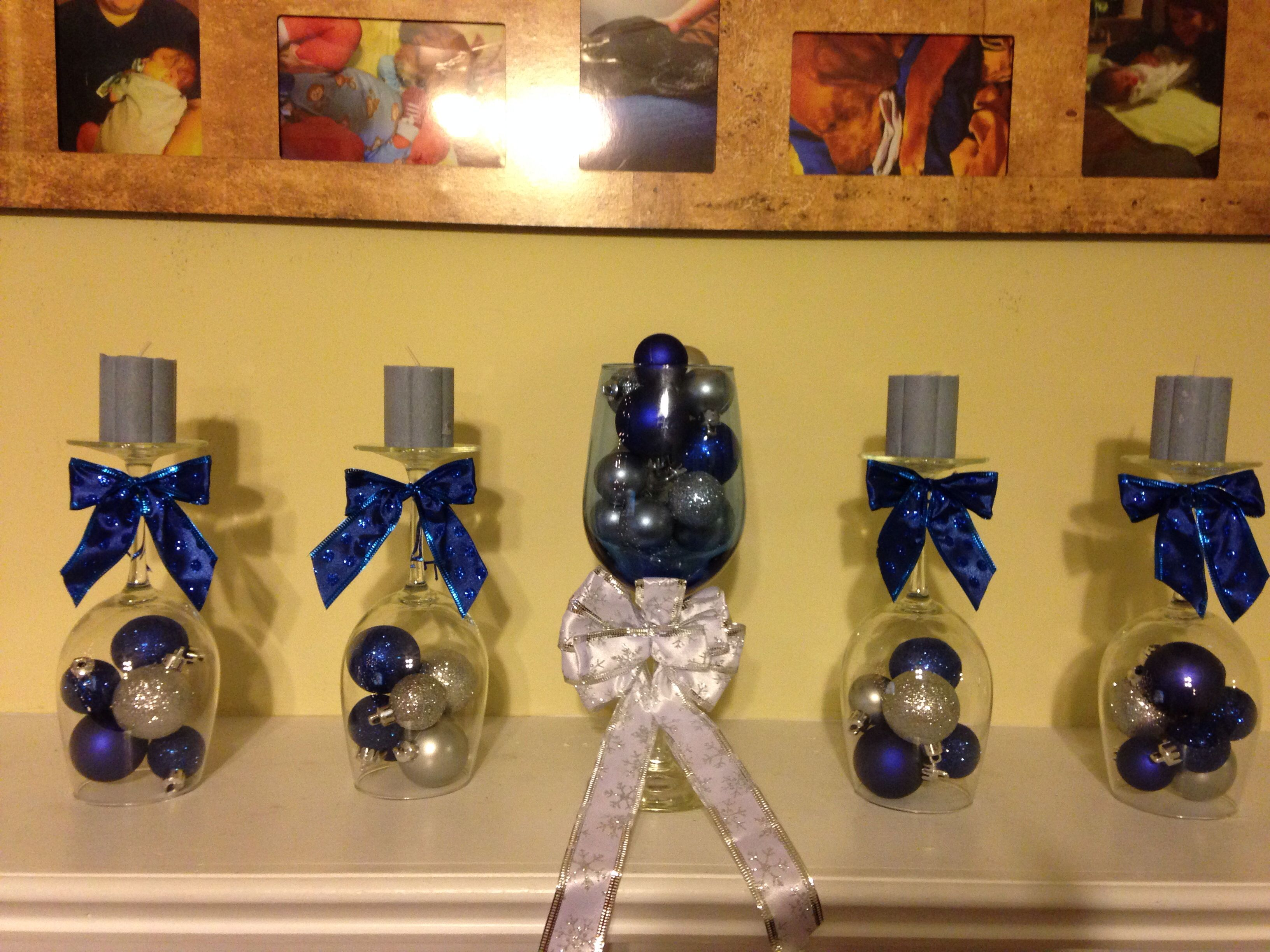 Mantle decoration for Christmas. Wine glasses, mini ornaments, candles and bows.