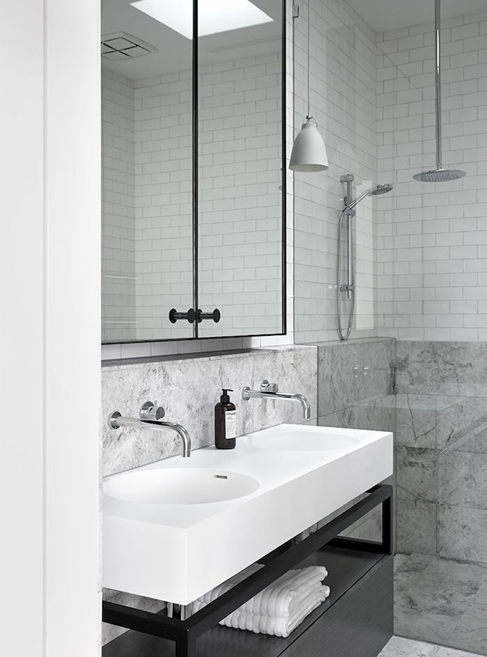 Grey and white bathroom: high ceiling, round chrome wall-mounted shower head, white bell-shaped pendant light, mirror cabinet, marble tiles on walls and floor, white handmade subway tiles, white full-width countertop with integrated his-and-her basins, black wood and metal vanity underframe with cabinet/drawer storage and open shelf for towels, frameless glass shower door