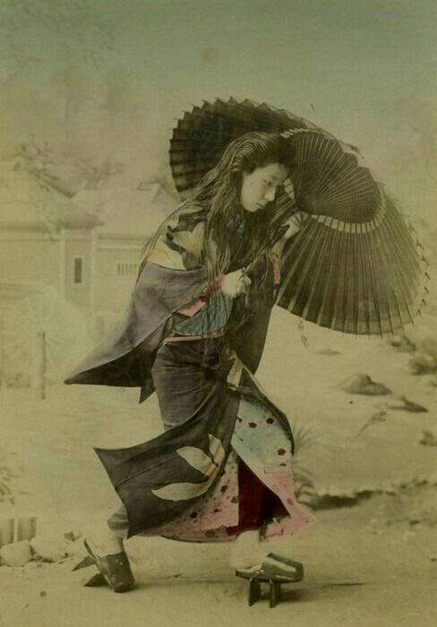 A Japanese woman fights the rain. Notice her long hair!