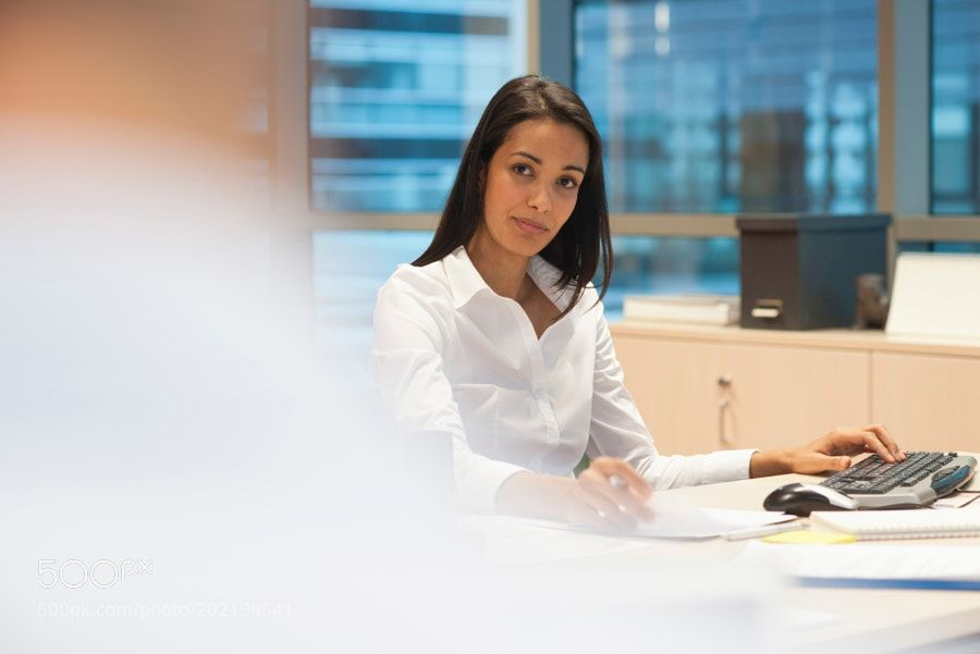 Businesswoman working in office by photoalto