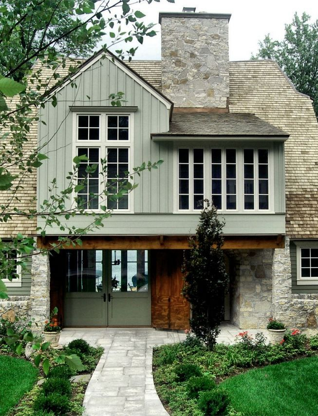 Pretty story house in neutral colors light sage painted wood white window trim oat roof gray stone front walkway surrounded by low green also rh pinterest