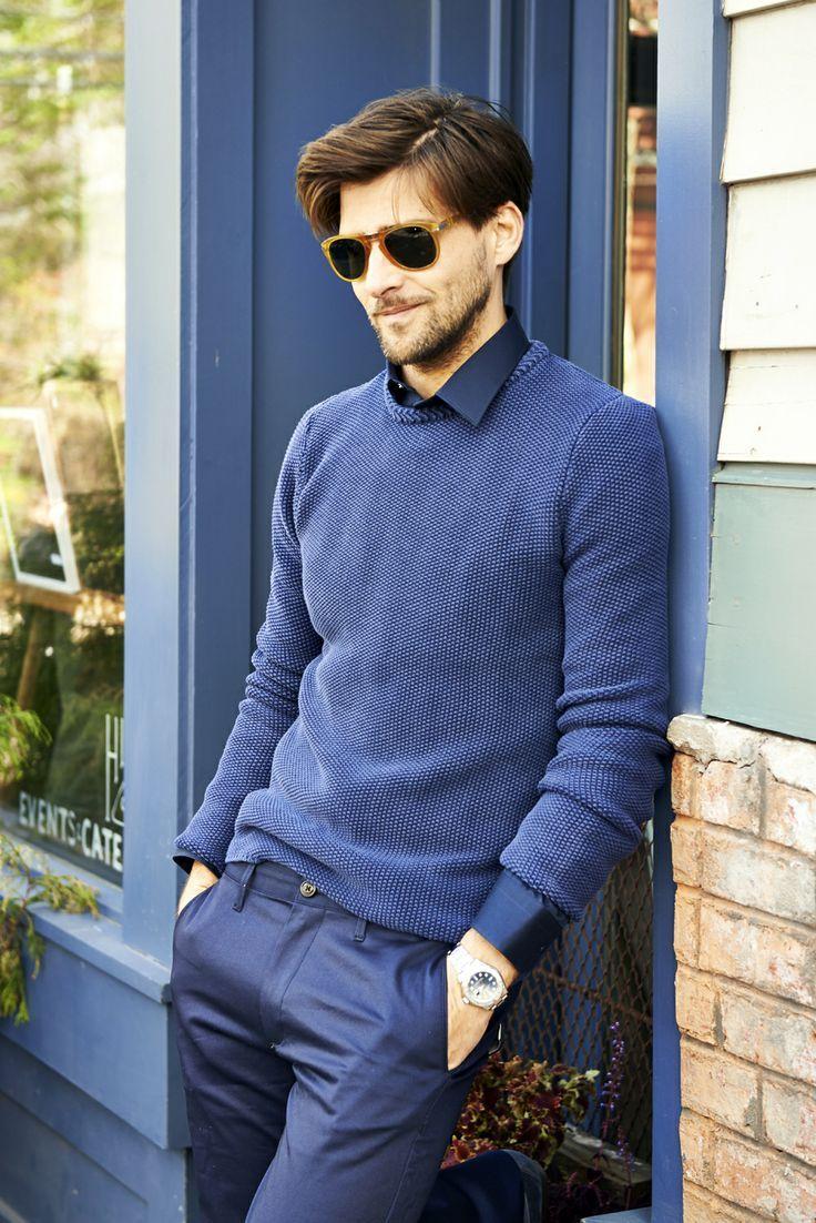 Johannes Huebl wearing Blue Crew-neck Sweater, Navy Long Sleeve Shirt, Blue  Dress Pants, Brown Sunglasses