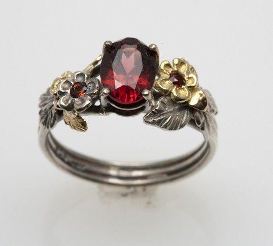 Floral design, gold, silver, garnet, and diamond. $330.00